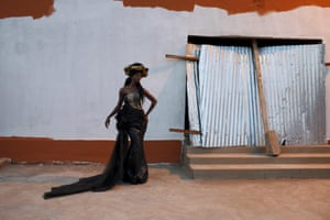 model wears a bazin dress, stands outside with painted wall as background
