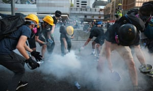 Protesters react after teargas was fired by police outside the central government complex in Hong Kong