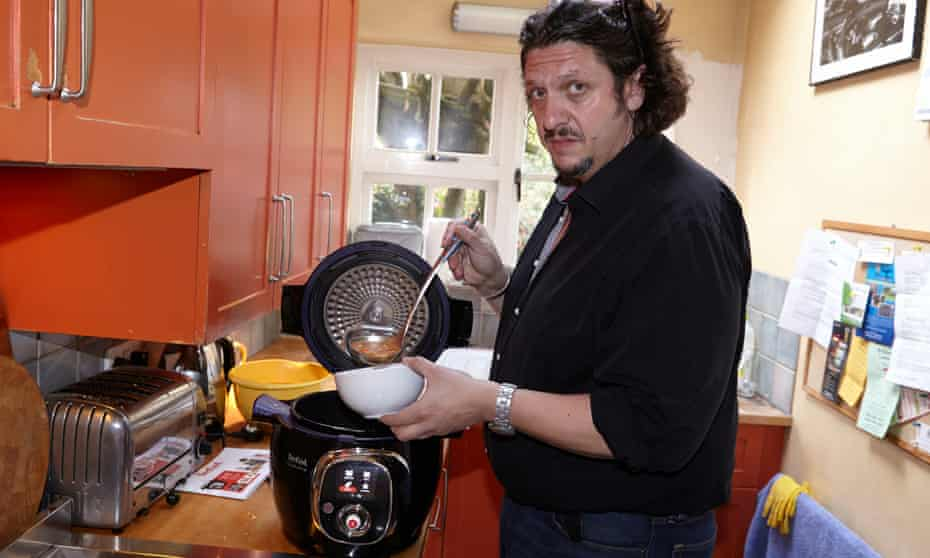 Jay Rayner spooning casserole into a bowl in his kitchen.