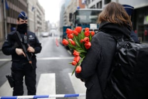 A woman arrives with flowers at a cordoned-off area near Maelbeek station