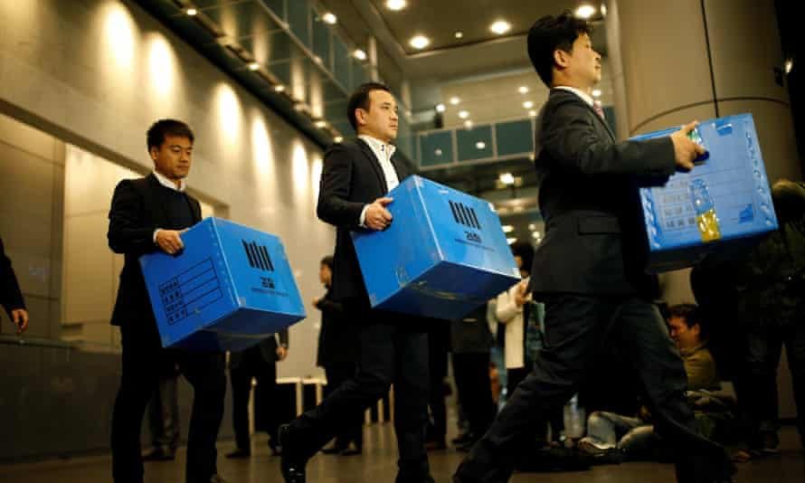Prosecution investigation officers walk out with boxes carrying evidence seized at Samsung in Seoul on Tuesday.