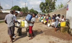 People line up to collect water from Pragosa, a Portuguese construction firm, in Maputo, Mozambique.