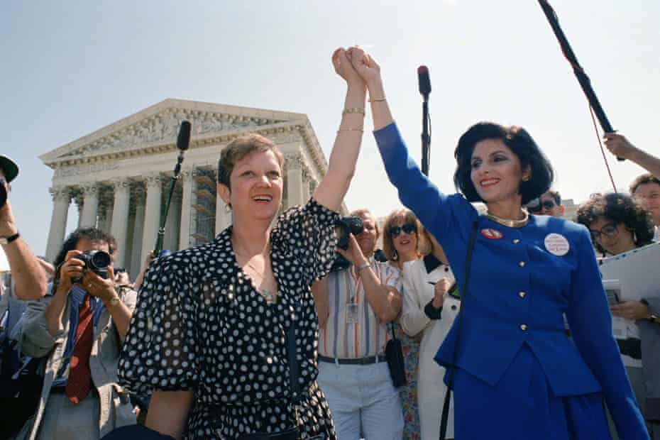 Norma McCorvey, Jane Roe in the 1973 court case, left, and her attorney Gloria Allred hold hands as they leave the Supreme Court building in Washington.
