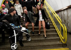 """Passengers not wearing pants walk down the stairs during an annual flash mob event called the """"No Pants Subway Ride"""" in Prague, Czech Republic"""