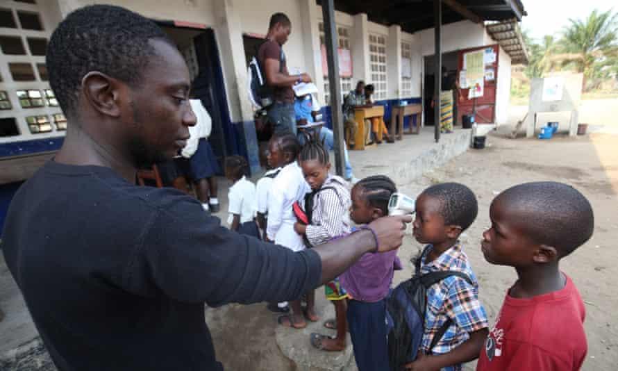 A Liberian health worker examines school pupils in Monrovia, 2015