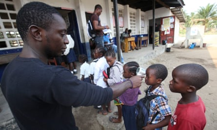 A Liberian health worker examines school pupils in Monrovia, 2015