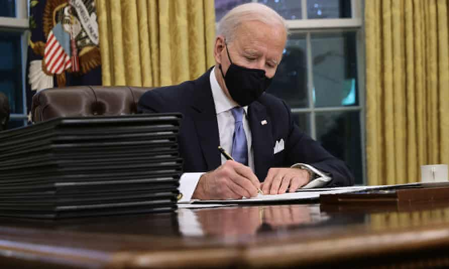 Joe Biden prepares to sign a series of executive orders at the Resolute desk.