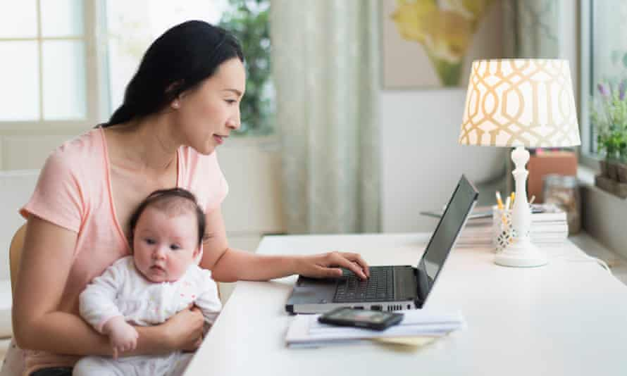 Asian mother with baby working from home.