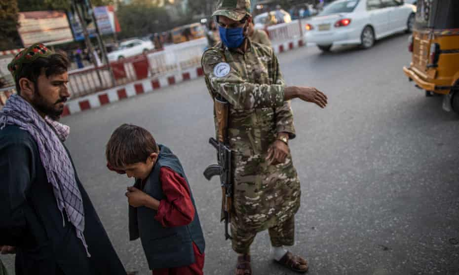 A Taliban police officer slaps a boy for loitering. Force is now supposed to be a last resort, according to Kandahar's new vice and virtue chief.