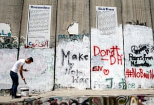 A young Palestinian checks his phone while painting the separation wall in Bethlehem to make space on the wall for tourists to spray their own messages near the new hotel set up by the British graffiti artist Banksy