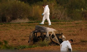 Forensic experts examine a field after a bomb blew up Daphne Caruana Galizia's car.