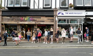 Holiday-makers queuing outside a surf clothing shop in Newquay, Cornwall, last week.