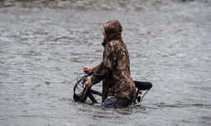A man walks his bicycle through a street flooded by Hurricane Sally in Pensacola, Florida.