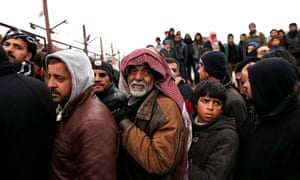 Syrian refugees wait for food near a refugee camp in Bab al-Salama city, northern Syria