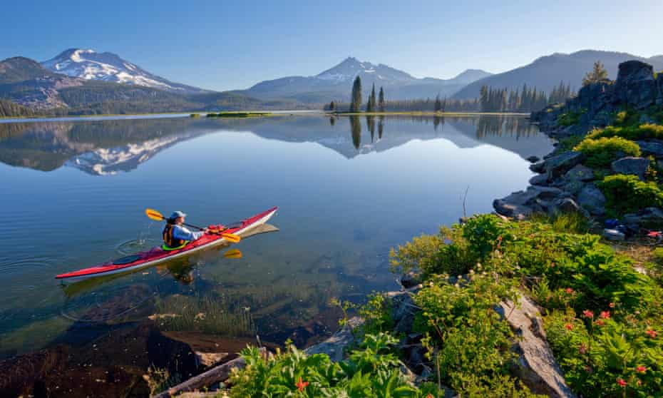 Woman kayaking on Sparks Lake, with South Sister and Broken Top in background, Oregon, USA Sparks Lake is a lake in Deschutes County, Oregon.