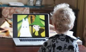 A boy watches TV on a laptop