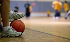 Basketball player holding ball with feet