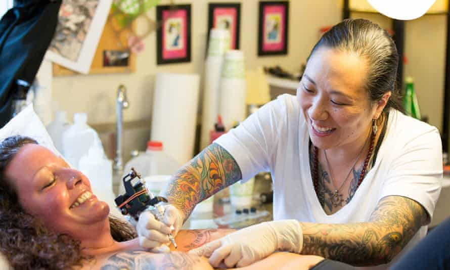 Amy Black tattoos a woman who has had breast surgery.
