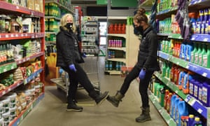 Two people wearing face masks greet by touching feet at the Homebase home improvement store in Rayleigh Weir.