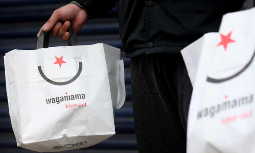 A Deliveroo worker collects an order from a Wagamama restaurant's deliveries entrance
