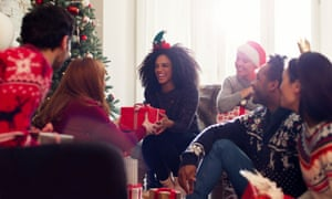 Smiling friends exchanging Christmas gifts in living room