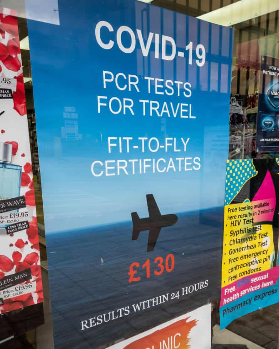 A poster in the window of a pharmacy offering commercial Covid-19 PCR test for travel.