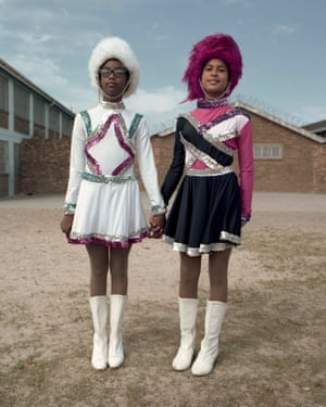 Jo-dean Martin, who is the drummies' team leader, and Ashnique Paulse, the team sub-leader wear pink and white busbys, signalling their senior positions in the team.