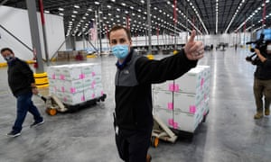 A worker gives a thumbs up while transporting boxes containing the Moderna Covid-19 vaccine
