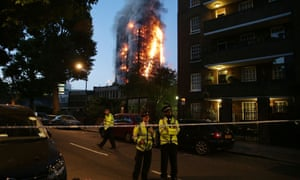 Police man a security cordon as the Grenfell Tower fire rages.