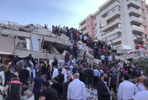 Rescue workers and local people try to reach residents trapped in the debris of a collapsed building in İzmir