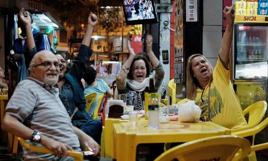People in a bar in Rio watching the Olympic opening ceremony