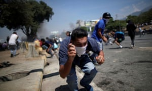 A masked opposition protester in Caracas. As the afternoon wore on, protesters battled security forces, throwing stones and facing rubber bullets in response.