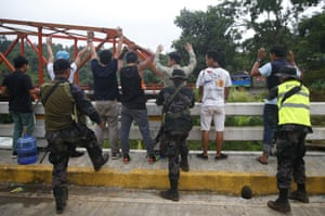 Male residents are frisked by police at a checkpoint as they leave Marawi