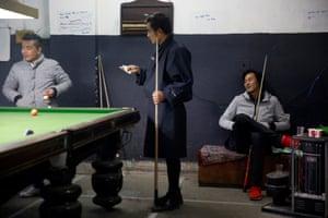 Men play snooker in a hall in Thimphu.