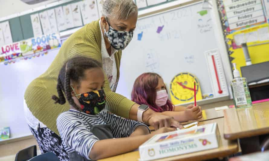Teacher Joy Harrison with her second-grade class at Carl B Munck elementary school in Oakland on Wednesday. The new policy applies to public and private schools.