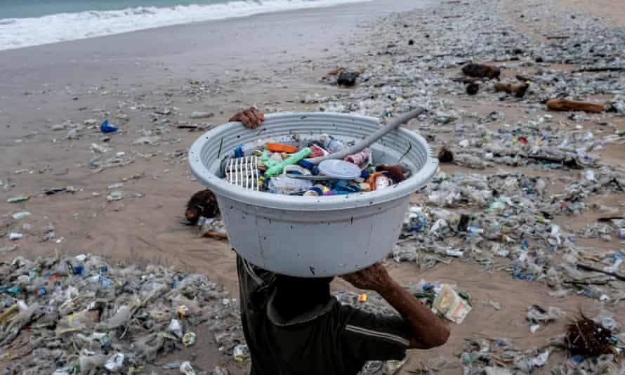 A woman collects recyclable plastics washed up on the beach in Bali, Indonesia.