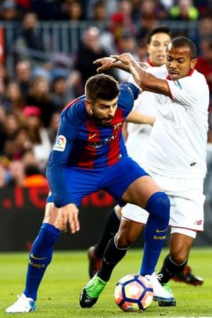 Gerard Piquegets the better of Sevilla's Mariano Ferreira.