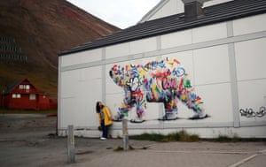 A woman poses next to a polar bear mural in Longyearbyen, the world's northernmost town.