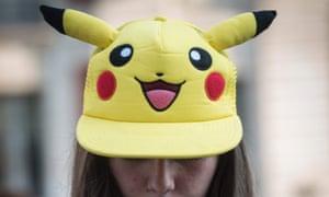 A girl sporting a Pikachu hat plays Pokemon Go