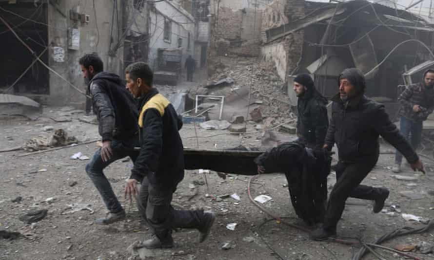 Syrian civil defence volunteers carry away an injured man in rebel-held eastern Ghouta.