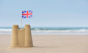 Union Jack flag in a sandcastle on a beach