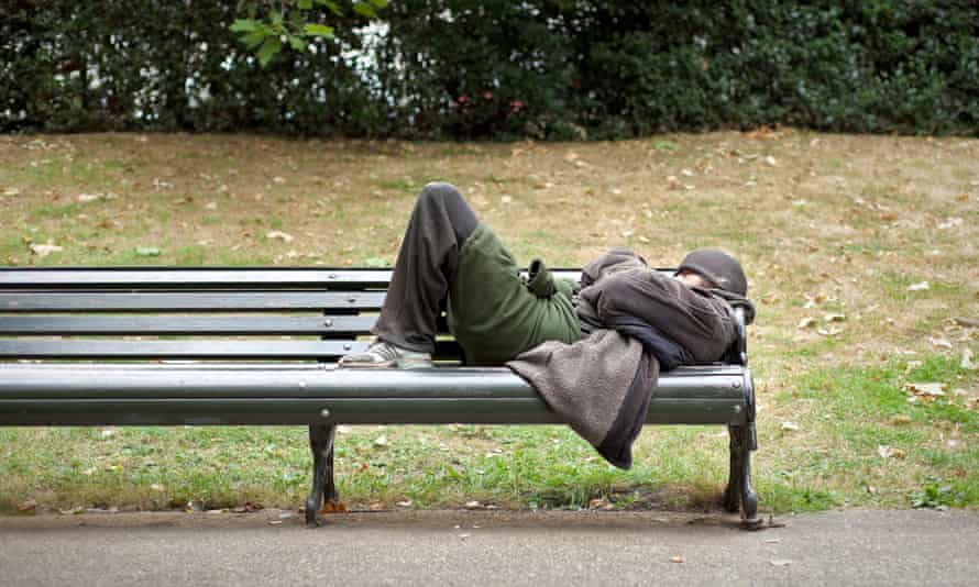 A homeless man sleeping on a bench in central London.