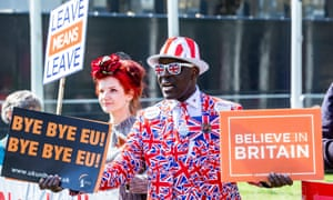 Man dressed in Union flag suit holds pro-Brexit placards