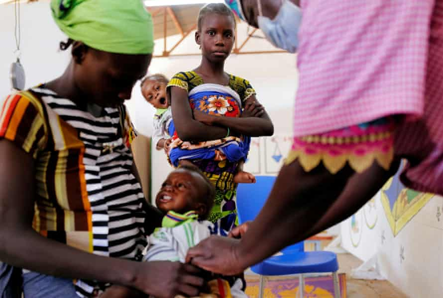 Zonabo Sore, 11, from Sahel region, carries her sixteen-month-old nephew Housein, who suffers from malnutrition