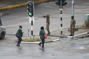 Armed soldiers stand on the road leading to President Robert Mugabe's office in Harare.
