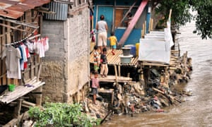 Children fish on a river bank in one of downtown Jakarta's slum areas next to public toilets.