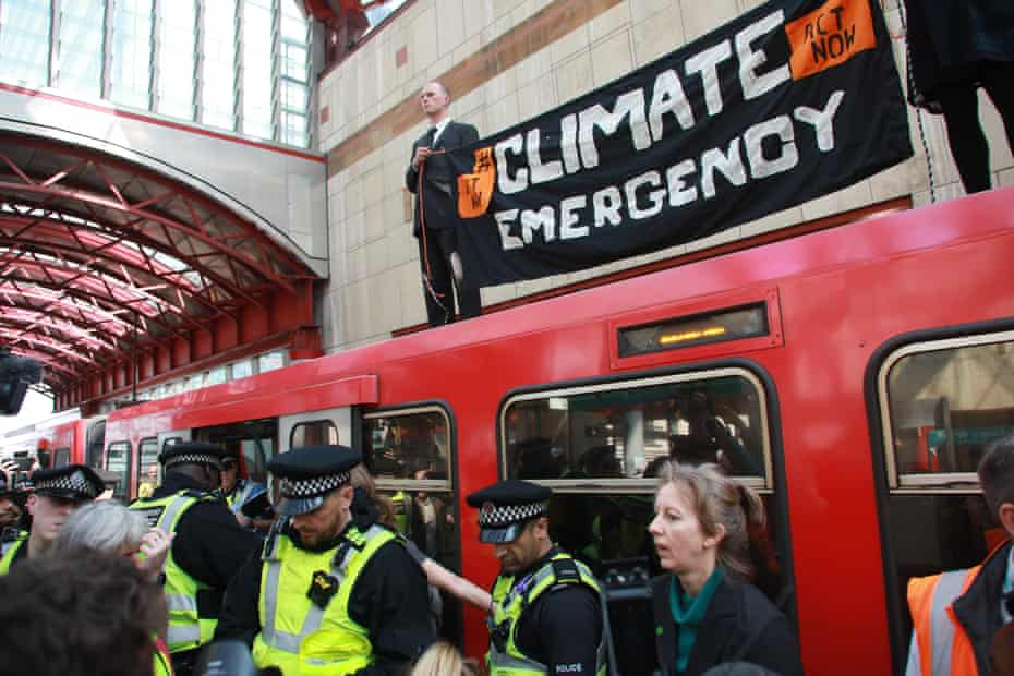 Activists climb on top of a DLR train at Canary Wharf in April