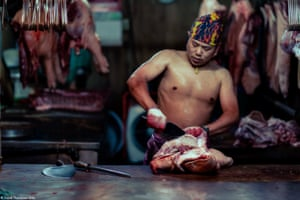 Taiwan 26. Action - David Thompson Stills - Head to Head - Taken at Wanhua District night market, Taipei, Taiwan the photo depicts a butcher preparing cuts for the daily traditional market, here seen working on a pigs head cutting out the cheeks.