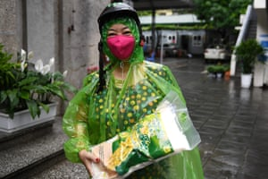 A woman wearing a bright pink face mask carries a bag of rice in Hanoi, Vietnam