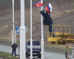 Workers put up North Korean and Russian flags on a road leading to the Far Eastern Federal University in Vladivostok